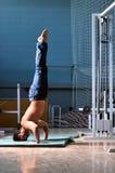 Homem novo que executa o handstand no estúdio da aptidão Imagem de Stock
