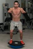 Homem novo que exercita - bola do equilíbrio de Bosu fotos de stock