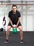 Homem novo que exercita com kettlebell Foto de Stock Royalty Free