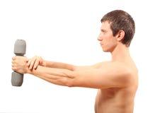 Homem novo que exercita com um dumbbell Imagem de Stock