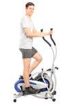 Homem novo que exercita em uma máquina transversal do instrutor Foto de Stock Royalty Free