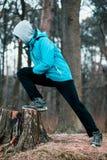 Homem novo que exercita fora em uma floresta entre as árvores leafless o Fotografia de Stock Royalty Free