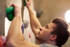 Homem novo que exercita na parede de escalada interna do gym Foto de Stock Royalty Free