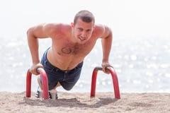 Homem novo que exercita na praia fotografia de stock royalty free