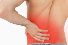 Homem novo que experimenta a dor nas costas Foto de Stock Royalty Free