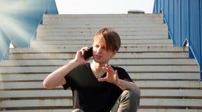 Homem novo que explica algo complicado, ao falar através do telefone, sentando-se nas escadas com cerca azul foto de stock royalty free