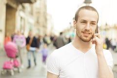 Homem novo que fala com passeio do telefone de pilha fotografia de stock royalty free