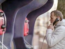 Homem novo que fala em um payphone vermelho da rua foto de stock
