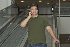 Homem novo que fala no smartphone Fotografia de Stock Royalty Free