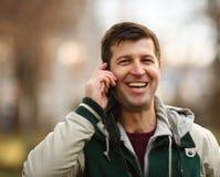Homem novo que fala no telefone ao ar livre fotografia de stock