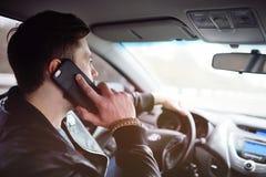 Homem novo que fala no telefone ao conduzir um carro imagens de stock royalty free