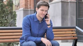 Homem novo que fala no telefone, assento exterior no banco filme