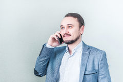 Homem novo que fala no telefone em um revestimento da sarja de Nimes no fundo cinzento Fotos de Stock
