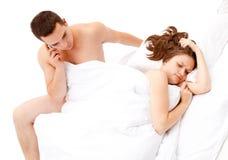 Homem novo que fala no telefone na cama imagens de stock royalty free