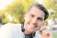 Homem novo que fala no telefone outdoors fotos de stock royalty free