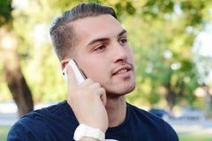 Homem novo que fala no telefone outdoors foto de stock royalty free