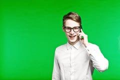 Homem novo que fala pelo telefone e que smiliing Imagem de Stock Royalty Free