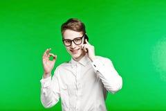 Homem novo que fala pelo telefone e que smiliing Imagens de Stock Royalty Free