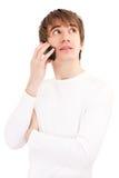 Homem novo que fala pelo telefone móvel Fotografia de Stock