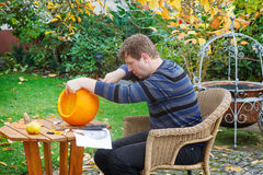 Homem novo que faz a abóbora de Halloween Foto de Stock