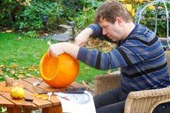 Homem novo que faz a abóbora de Halloween Foto de Stock Royalty Free