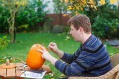 Homem novo que faz a abóbora de Halloween Fotografia de Stock Royalty Free