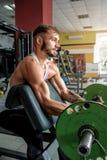 Homem novo que faz exercícios do bíceps no gym foto de stock royalty free
