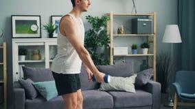 Homem novo que faz exercícios dos esportes com o peso em casa que levanta dar certo do braço video estoque