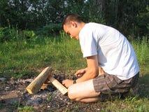 Homem novo que faz a fogueira fotografia de stock royalty free