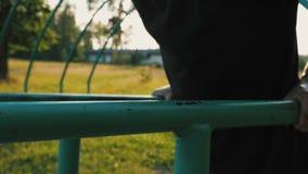 Homem novo que faz impulso-UPS das barras paralelas no campo de jogos em um parque público natural video estoque