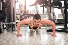 Homem novo que faz impulso-UPS no gym Fotografia de Stock