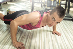Homem novo que faz impulso-UPS no gym Fotografia de Stock Royalty Free