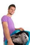 Homem novo que faz a lavanderia Fotografia de Stock Royalty Free