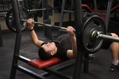 Homem novo que faz o exercício da imprensa de banco no gym Fotos de Stock