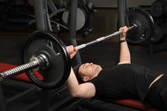 Homem novo que faz o exercício da imprensa de banco no gym imagens de stock