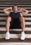 Homem novo que faz o exercício do Abs Fotos de Stock Royalty Free