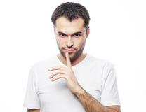 Homem novo que faz o gesto do silêncio, shhhhh!! foto de stock