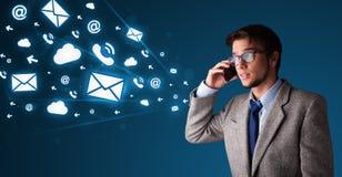 Homem novo que faz o telefonema com ícones da mensagem Fotografia de Stock