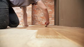 Homem novo que faz os reparos que pintam o assoalho de madeira dentro video estoque