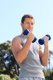 Homem novo que faz seus exercícios Fotografia de Stock Royalty Free