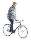Homem novo que faz truques em bicicleta fixa da engrenagem em um branco imagem de stock