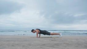 Homem novo que faz um cruz-treinamento na praia O indivíduo pressiona e faz um backflip na praia no fundo do video estoque