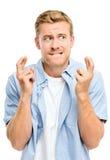 Homem novo que faz um desejo isolado no fundo branco Imagens de Stock