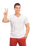 Homem novo que faz um gesto de mão da paz Imagens de Stock