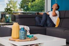 Homem novo que faz um telefonema e que ri alto no sofá foto de stock