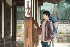 Homem novo que faz uma viagem backpacking em uma casa tradicional coreana fotos de stock