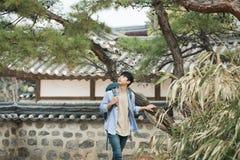 Homem novo que faz uma viagem backpacking em uma casa tradicional coreana imagens de stock royalty free