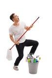 Homem novo que finge jogar a guitarra em um espanador Imagem de Stock Royalty Free