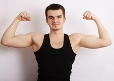 Homem novo que flexiona seus músculos Imagens de Stock Royalty Free