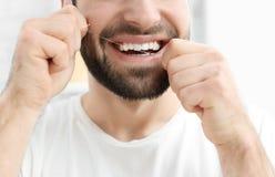Homem novo que flossing seus dentes imagens de stock
